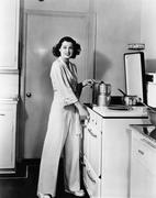 Portrait of woman at stove in kitchen Stock Photos