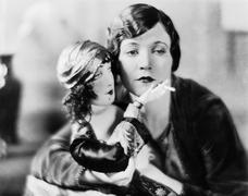 Woman with doll holding cigarette Stock Photos