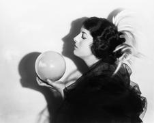 Profile of dramatic woman holding sphere Stock Photos