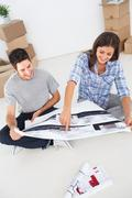 Woman and her husband looking at their house plans - stock photo