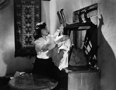 Woman barring door with furniture Stock Photos