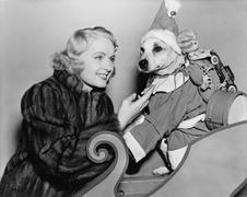 Woman with dog in Christmas outfit - stock photo