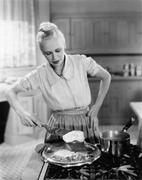 Woman flipping eggs on stove - stock photo