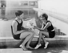 Couple sitting with their puppy next to a pool Stock Photos
