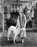 Young woman in coat and hat standing outside with her Russian Wolfhound - stock photo