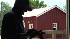 Farmer using a tablet on his farm, silhouette - stock footage