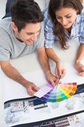 Couple looking at a color chart to decorate their house - stock photo