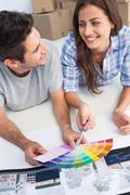Happy couple looking at a color chart to decorate their house - stock photo