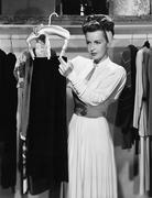 Young woman hanging up a skirt in the closet Stock Photos