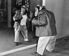 Chimpanzee in a jacket and trousers in front of a mirror - stock photo