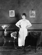 Young woman in an apron and a duster standing in a living room Stock Photos