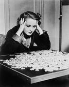 Young woman trying to solve a puzzle Stock Photos