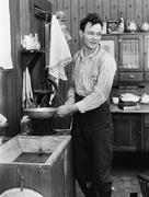 Man in a kitchen pumping water Stock Photos