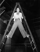 Young woman climbs a ladder to the top Stock Photos