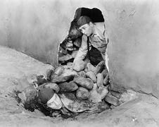 Two men crawling out of a hole in a wall - stock photo