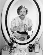 Woman sitting in front of her vanity looking into the mirror - stock photo