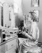 Woman sitting in front of her vanity putting perfume on her eyebrows Stock Photos