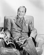 Man sitting on an armchair reading a magazine Stock Photos