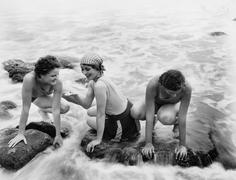 Three women playing in water on the beach Stock Photos