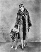 Woman in her Giraffe patterned fur coat and her dog - stock photo