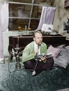 Man sitting on a bed smoking his water pipe Stock Photos