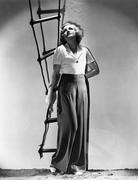 Young woman holding a rope ladder and looking up Stock Photos
