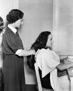 Profile of a female hairdresser cutting a young woman's hair Stock Photos