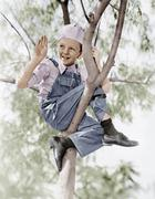 Low angle view of a boy sitting on a tree Stock Photos