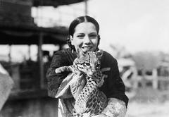 Portrait of a young woman carrying a cheetah cub and smiling Stock Photos