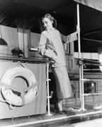 Young woman standing at the railing of a boat Stock Photos