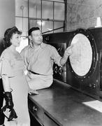 Man explaining about radar to a young woman in a control room Stock Photos