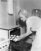 Young woman taking cookies out of an oven Stock Photos