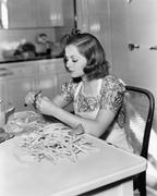 Young woman sitting on a chair and cutting beans Stock Photos