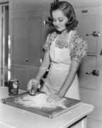 Young woman pouring water into flour Stock Photos