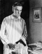 Man holding a handgun in a handkerchief looking distraught - stock photo