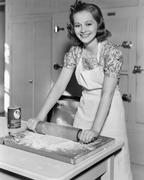 Young woman rolling out dough in the kitchen Stock Photos