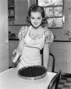 Portrait of a young woman preparing a blueberry pie in the kitchen Stock Photos
