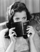 Portrait of a young woman holding a diary and thinking - stock photo