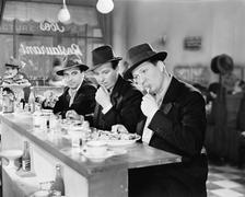 Three men with hats eating at the counter of a diner Stock Photos