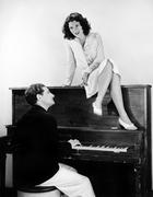 Woman singing on an upright piano with a friend playing Stock Photos