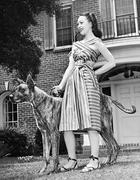 Young woman standing with her Great Dane in a courtyard - stock photo