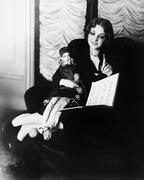 Woman sitting in an armchair with her puppet reading a book Stock Photos
