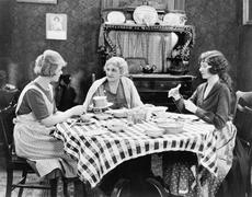 Three women sitting at the dining table talking Stock Photos