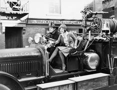Firefighter driving a fire engine and a young woman sitting beside him Stock Photos