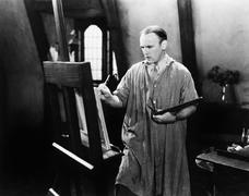 Man painting on an easel with a paintbrush Stock Photos