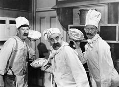Three chefs holding pies for a fight in the kitchen Stock Photos