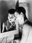 Profile of a young man in front of a mirror in a bathroom shaving - stock photo