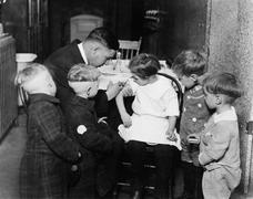Pediatrician immunizing a little girl while other children are watching Stock Photos