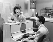 Profile of a young man playing a piano with a young woman standing in front - stock photo