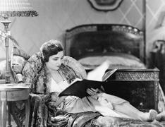 Nuori nainen makuuasentoon nojatuoli ja lukee kirjaa hänen makuuhuoneessa Kuvituskuvat
